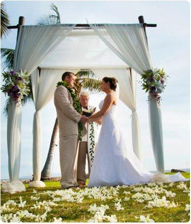 A destination weddingin Maui under a bamboo chuppa wedding arche.