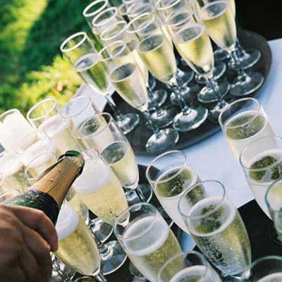 Bar service with champagne pouring at a catered Maui wedding reception at the Olowalu plantation house.