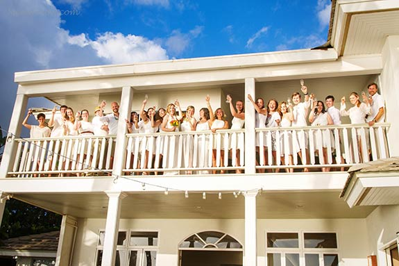 A Maui wedding photograph of the guests on the balcony of the White House beach front private estate wedding venue in Lahaina.