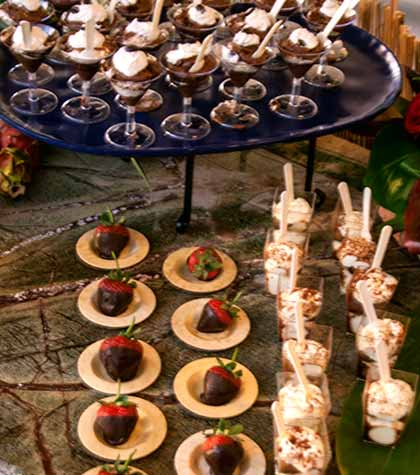 Catered dessert station with chocolate strawberries and coffee chocolate mousse.