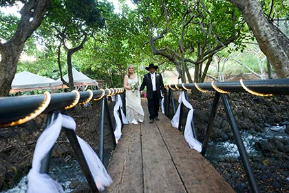 A country wedding on Maui with a bridge and stream on a ranch.