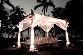 Wedding reception using a wedding chuppah as a dining canopy during a wedding reception on Maui.