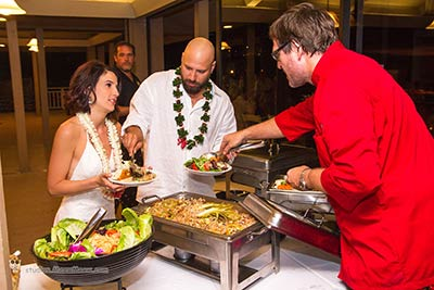 Maui chef CJ serving guests in the buffet line at a catered wedding reception.