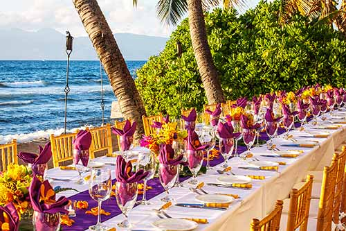 Maui oceanfront dinning with a table setting for 40 at a beach wedding in Lahaina.