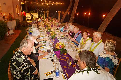 A catered Maui wedding reception in Lahaina with guests seated at a single table.
