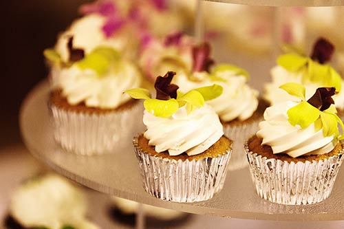 Cupcakes for a wedding in Lahaina are garnished with edible flowers.