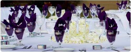 A wedding table setting complete with linens, silverware, china and more at a catered Maui wedding in West Maui.
