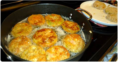 Fried green tomatoes cooking in oil in Maui kitchen.