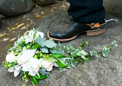 A bridal bouquet alongside a boot with a spur for a country wedding on Maui.