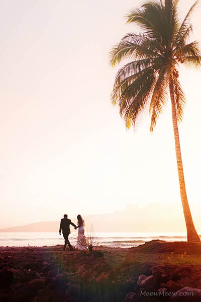 A couple is photographed in the sunset after their Maui wedding ceremony.