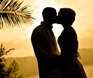 A newlywed couple first kiss at a sunset beach wedding on Maui.