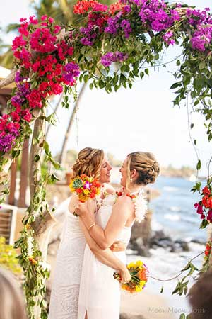 A Maui wedding with a drift wood arch covered in bougainvillea flowers.
