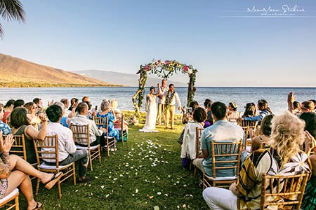 An oceanfront wedding on Maui with a flower covered arch.