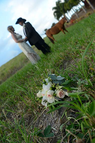 The bride and groom with the bridal bouquet and horses in the ranch pasture on Maui.