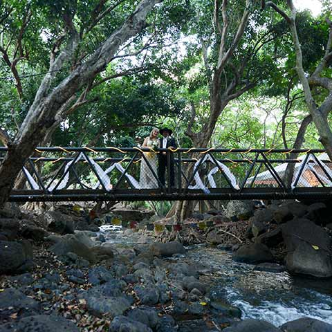 A Maui wedding couple on a bridge over a stream on Makani Olu Ranch.