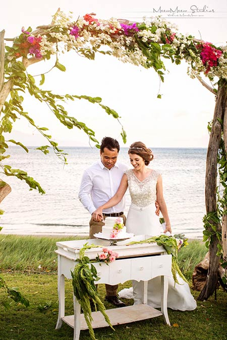 A newlywed couple cutting their tropical floral topped wedding cake on a vintage desk and under a flower draped chuppah at an oceanfront wedding venue on Maui.