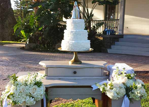 A Olowalu Plantation House catered wedding reception with a white wedding cake and kissing couple surfboard cake topper.