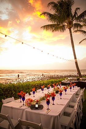 Oceanfront Maui wedding receptions with blue glasses, orange napkins and white linen table clothes.