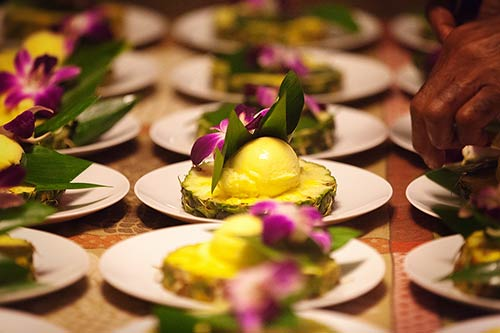 Maui catering preparing pineapple sorbet boats garnished with purple orchid.
