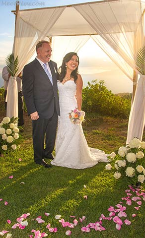 A couple getting married on Maui under a bamboo chuppa with fresh flower pedals.