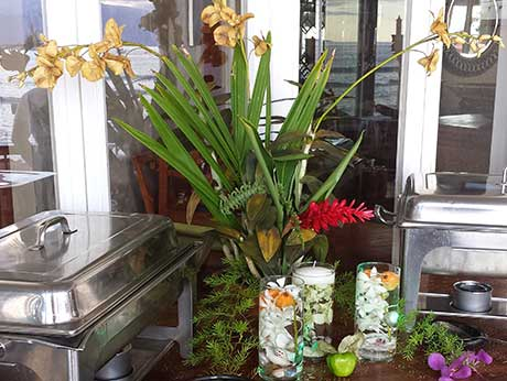 Tropical Maui wedding flowers including yellow orchids, pink ginger and white plumeria in vases on catering buffet table.