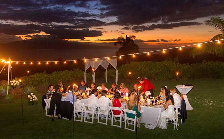 A Maui wedding reception dinner with the sunset in the background.