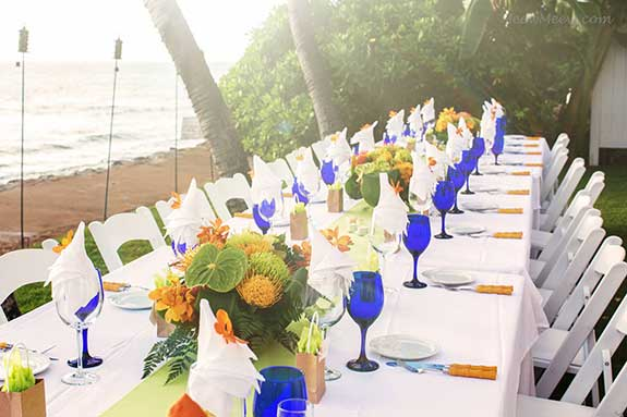 A kings table set for an oceanfront wedding in Lahaina set with cobalt blue glasses and lime green linen runners on a white table cloth.