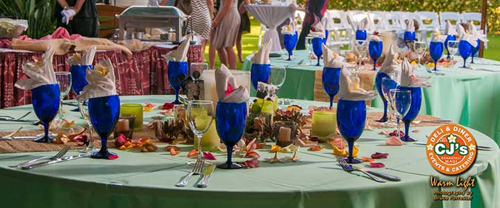 A catered wedding buffet table with turquoise tablecloth and blue glassware