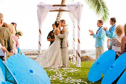 A Maui wedding at the Olowalu Plantation House with blue umbrellas and a bamboo chuppah.