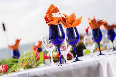 Orange napkins, blue glasses and white linen tablecloths for a Maui wedding reception.