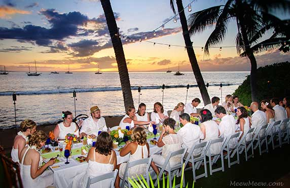 A Maui wedding reception enjoying beach front dining in Lahaina at the White House private estate.